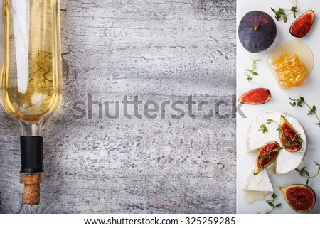 Cheese Board,appetizer.Brie cheese,Camembert,bottle of white wine,figs,honey and thyme and white wine.Copy space.selective focus - stock photo