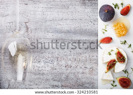 Cheese Board,appetizer.Brie cheese,figs,blueberries,honey and thyme and white wine.Copy space.selective focus - stock photo