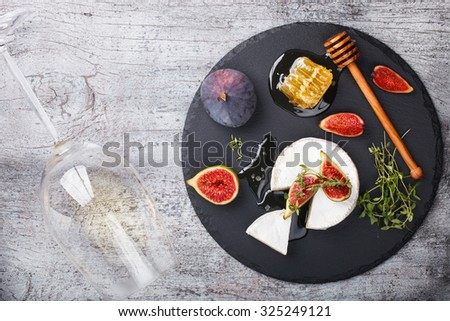Cheese Board,appetizer.Brie cheese,figs,blueberries,honey and thyme and white wine.selective focus - stock photo