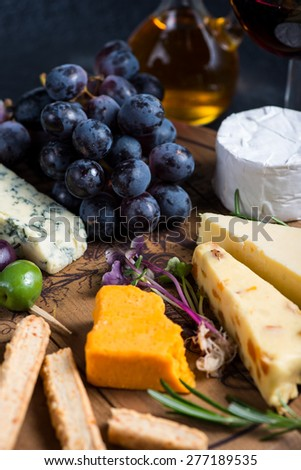 Cheese board with fresh grapes,herbs and olives, red wine