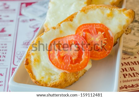 Cheese bread with tomato on top in white dish - stock photo