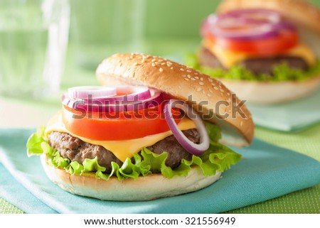cheese burger with beef patty lettuce onion tomato - stock photo