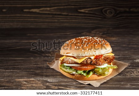 Cheese burger with grilled meat, cheese, tomato, on craft paper on wooden surface. Fast food template. Real photo. ideal for advertisement