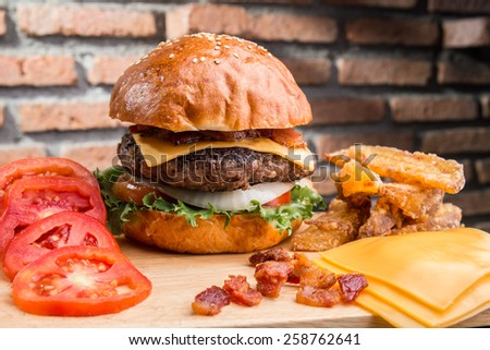 Cheese burger with ingredients around and brick background - stock photo