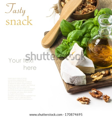 Cheese Camembert, walnuts, fresh basil and olive oil served on wooden board over white with sample text