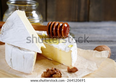 Cheese camembert with sweet honey on a wooden board. Gourmet food - stock photo