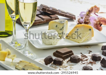 Cheese, chocolates, wine, and orchid on white - stock photo