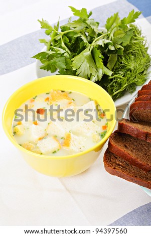 Cheese cream soup in yellow bowl with sippets bread and greens at side
