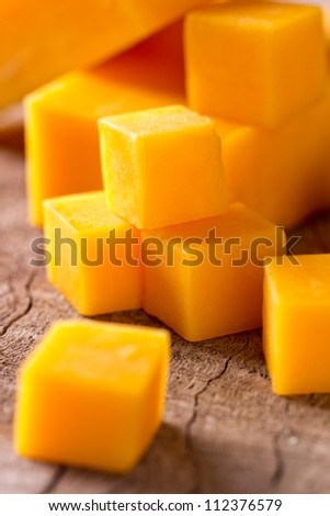 Cheese cubes on wooden background - stock photo
