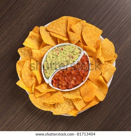 Cheese flavored nachos with guacamole (sauce based on avocado) and tomato salsa - stock photo