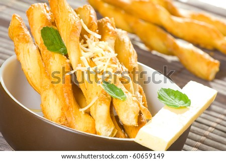 Cheese flavored salty twisted sticks on table cover with mint leaves. - stock photo