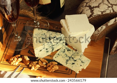 Cheese, glasses of wine and nuts on the board