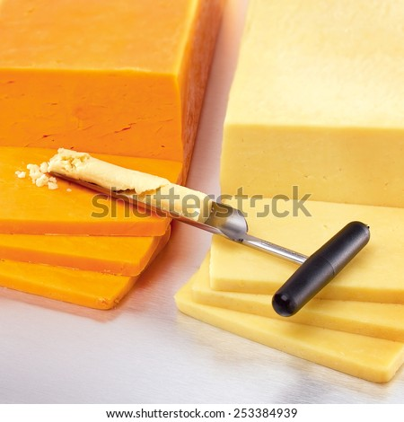 Cheese grading iron trier tester on sliced blocks of vintage cheddar showing crumbled cheese in trough of tool from bore test hole  - stock photo