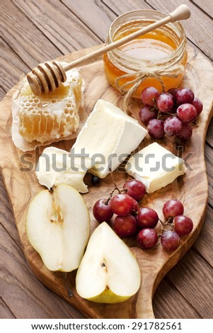 Cheese, grape and honey on wooden board