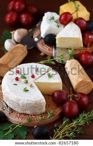 Cheese, grapes and herbs on a wooden board. - stock photo