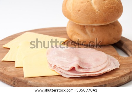 Cheese, ham and bread prepared for making sandwiches. - stock photo