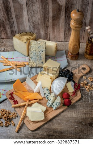 Cheese heaven. Cheese Mix Cheese brie, gouda cheese, blue cheese, cheese marmezan, orange cheese on a wooden board - stock photo