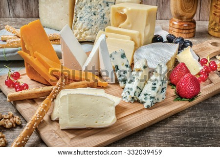 Cheese heaven. Cheese Mix Cheese brie, gouda cheese, blue cheese, cheese parmezan, orange cheese on a wooden board - stock photo