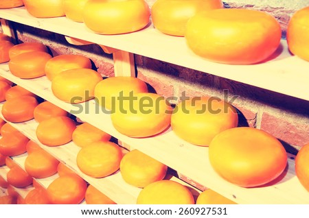 Cheese Kebbuck store with gouda cheese rack in refining in Amsterdam, the Netherlands. Concept photo of cheese making in food manufacturing. Vintage filter. - stock photo