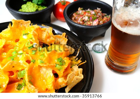 Cheese nachos with sides of guacamole and salsa with an ice cold bottled beer poured in a glass