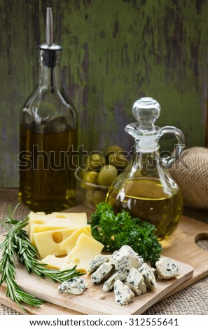 Cheese of two kinds on a cutting board, two bottles of olive oil, green olives in a glass bowl, and branches of rosemary and parsley.