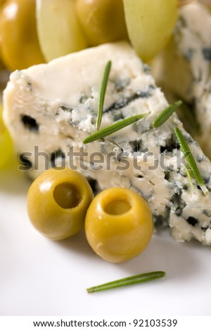 Cheese, olives and grapes - stock photo