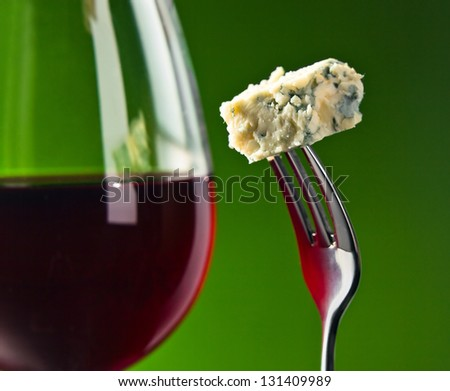 Cheese on a fork and glass with red wine - stock photo