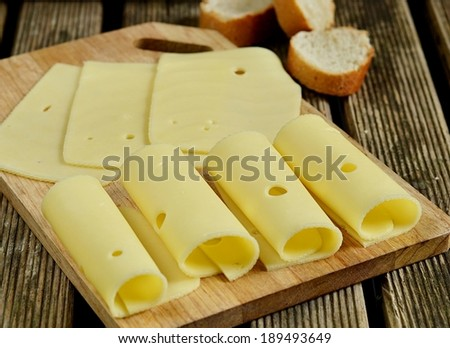 Cheese on a wooden cutting board with bread. Rustic style. Selective focus