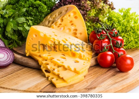Cheese on a wooden table against the background of nature. Maasdam, Brie, Parmesan cheese, gouda. Organic health food rich in calcium and minerals. - stock photo