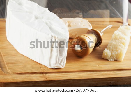 Cheese over wooden chopping board, close up, horizontal image - stock photo