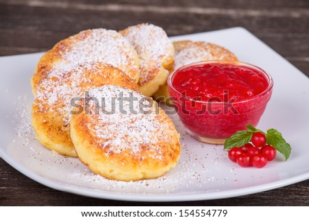 Cheese pancakes with berry jam and cinnamon in white plate - stock photo