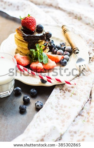 Cheese pancakes with fresh strawberry and blueberry fruits and chocolate for breakfast