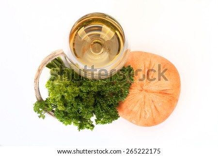 Cheese, parsley sprig and a glass of white wine on a white background. - stock photo