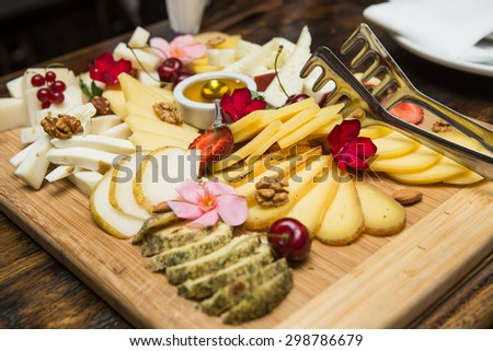 Cheese plate Assortment of various types of cheese on wooden cut - stock photo