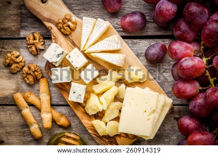 Cheese plate: Emmental, Camembert cheese, blue cheese, bread sticks, walnuts, grapes on wooden table - stock photo