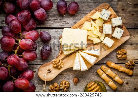 Cheese plate: Emmental, Camembert cheese, blue cheese, bread sticks, walnuts, hazelnuts, honey, grapes on wooden table - stock photo
