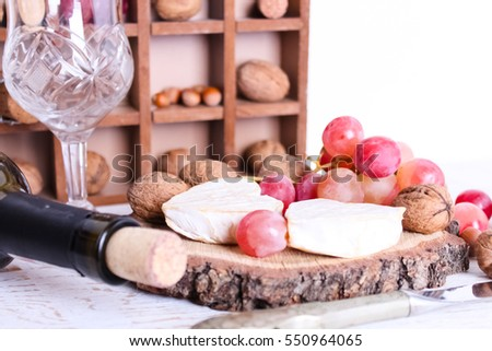 cheese plate on a wooden table with wine ,glass of red wine, Valentine's Day