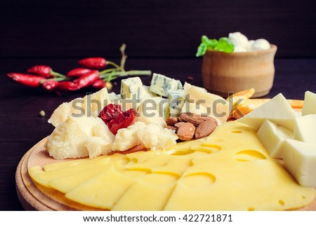 Cheese plate:Parmesan, cheddar, gouda, blue cheese, mozzarella and other with chili pepper and almond on wooden board. Tasty appetizer. Plate of cheese on wooden plate at a restaurant.Selective focus. - stock photo
