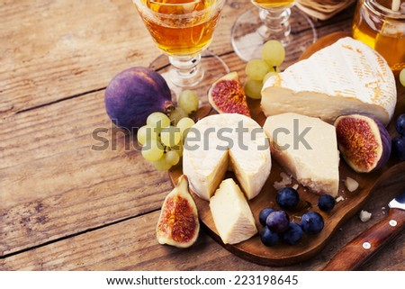 Cheese plate. Variety of cheese sorts with grapes and figs - stock photo