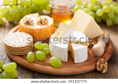 cheese plate with camembert, cheddar, grapes and honey - stock photo