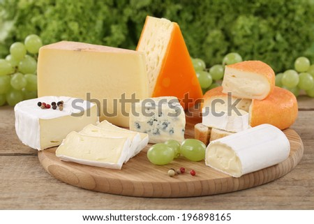 Cheese plate with Camembert, mountain and Swiss cheese on a wooden board - stock photo