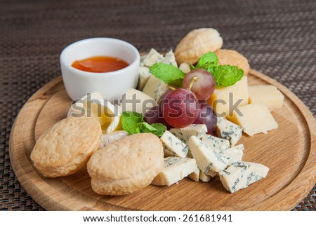 Cheese plate with cheeses Dorblu, Parmesan, Brie, Camembert and Roquefort with Grapes, Cookies and Sweet Sauce serving on wooden cutting boardtable close-up - stock photo