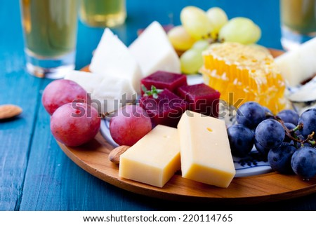 Cheese plate with fresh grape, honey comb, nuts and plum jelly, marmalade on  a blue wooden background - stock photo