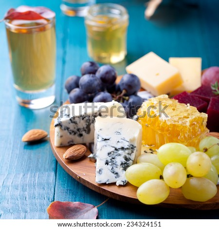 Cheese plate with fresh grape, honey comb, nuts and plum jelly, marmalade on a blue wooden background
