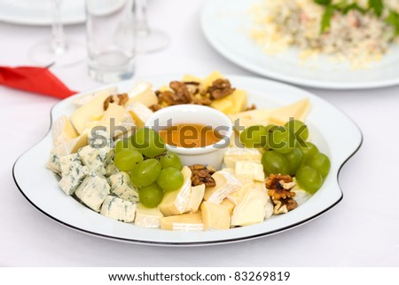 Cheese plate with nuts and honey on restaurant table - stock photo
