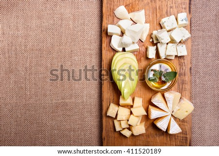 Cheese platter garnished with honey, apple and spice on rustic wooden board - stock photo