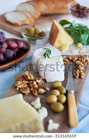 Cheese platter starter appetiser pre-dinner snack, assortment of different cheeses, nuts, olives and grapes - stock photo