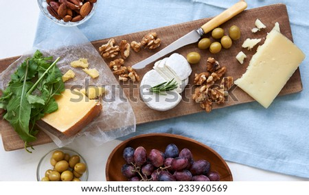 Cheese platter starter appetizer party snack, assortment of different cheeses, nuts, olives and grapes - stock photo