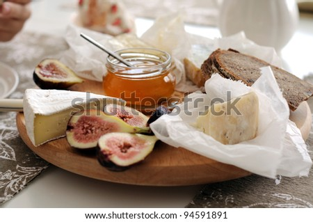 Cheese platter with French cheeses, honey  and figs - stock photo