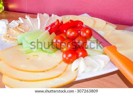 Cheese platter with fruits and vegetables / cheese plate garnished. - stock photo